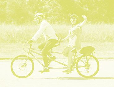 Green colored image of a man and a teenage girl on a tandem bike. Both of them are smiling and the girl uses one hand to wave toward the camera