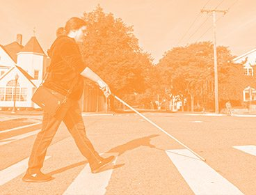 Orange colored image of a woman crossing a street with a white cane